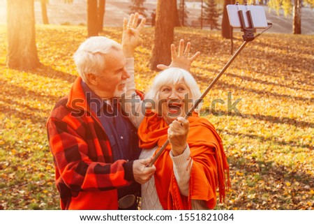 Positive mature couple showing tongues, laughing and fooling around while taking selfie pictures in the park #1551821084