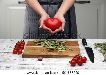 a heart-shaped tomato. a woman's hands hold a heart-shaped tomato against a gray black-striped apron on a white kitchen. cooking healthy food. Love and health concept. cook with love. #1551858290