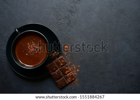 Homemade hot chocolate with winter spices in a black cup on a dark slate, stone or concrete background. Top view with copy space.