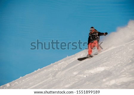 Snowboarder guy with dreadlocks riding down the hill in the popular tourist resort Gudauri in Georgia #1551899189
