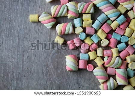 Marshmallows. Background or texture of colorful mini marshmallows. on a gray background,  With space to write titles, information or expressive words, - Image #1551900653
