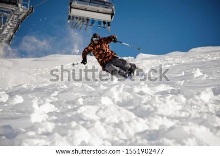Skier man riding down the hill under the ski lift in the popular tourist resort Gudauri in Georgia #1551902477