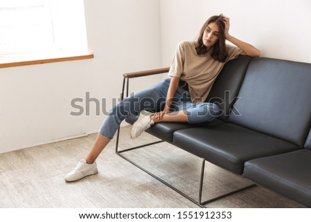 Image of positive pleased young amazing woman posing indoors at home on sofa. #1551912353
