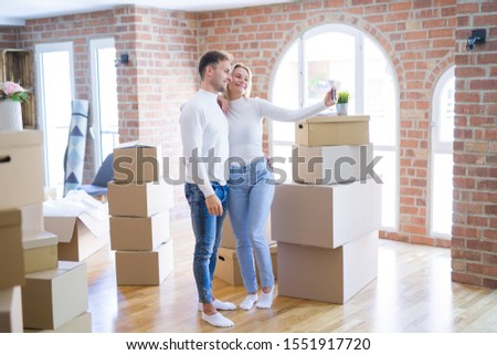 Young beautiful couple standing using smartphone to take selfie at new home around cardboard boxes #1551917720