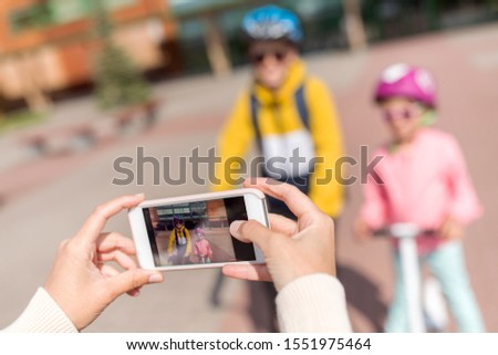 education, childhood and people concept - close up of hands taking picture of school children in helmets with backpacks and scooters by smartphone outdoors