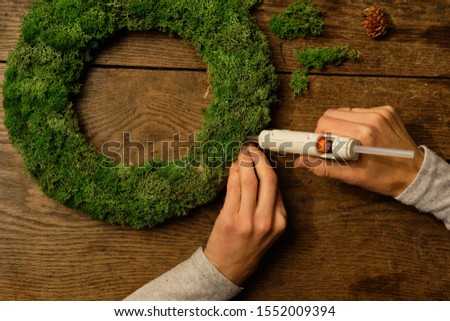 Woman glues moss on a wreath. Creating eco-wreaths in a trend #1552009394
