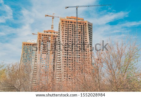 Building complex of high-rise buildings with turret slewing crane in the city. It is autumn, daytime with blue sky #1552028984