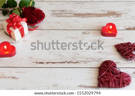 Red roses with hearts and candles on wooden background. St. Valentines Day or Wedding card concept with copy space for your text. #1552029794
