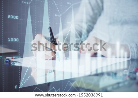 Hand taking notes in notepad. Forex chart holograms in front. Concept of research. Multi exposure #1552036991