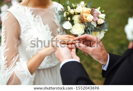 Wedding engagement rings. Married couple exchange wedding rings at a wedding ceremony. Groom put a ring on finger of his lovely wife. Concept wedding details. Happy family. Together. #1552043696