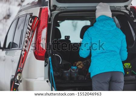 KAZKOVA POLYANA, UKRAINE - January 26, 2019: woman gathering to ski. car with opened trunk #1552046963