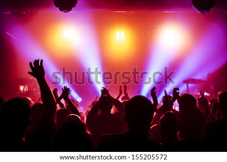 silhouettes of concert crowd in front of bright stage lights #155205572