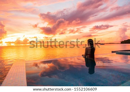 Paradise sunset idyllic vacation woman silhouette swimming in infinity pool looking at sky reflections over ocean dream. Perfect amazing travel destination in Bora Bora, Tahiti, French Polynesia. Royalty-Free Stock Photo #1552106609