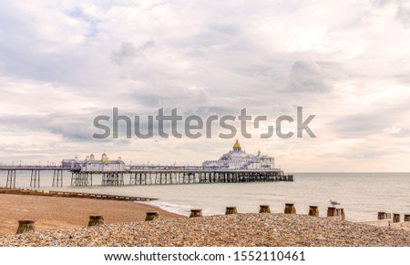 Early morning at a shingle beach in Eastbourne.  A wooden breakwater is in the foreground and a pier beyond. A dawn sky is above. #1552110461