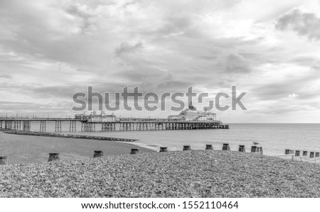 Early morning at a shingle beach in Eastbourne.  A wooden breakwater is in the foreground and a pier beyond. A dawn sky is above. #1552110464