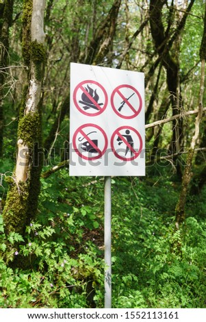 pictograms-pointers with a ban on fire, hunting, fishing and throwing garbage in a yew-Box grove in the Khostinsky district of Sochi. Russia, Krasnodar region #1552113161