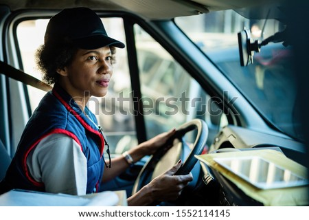 African American female courier driving delivery van in the city.  Royalty-Free Stock Photo #1552114145