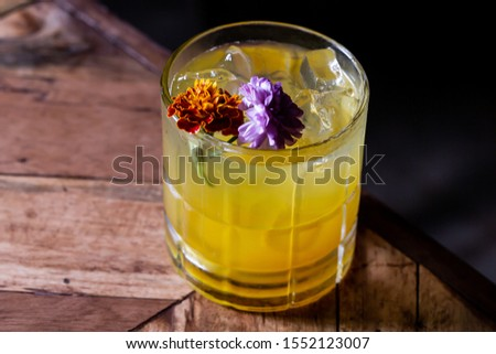 Flower garnished yellow cocktail on wood table #1552123007