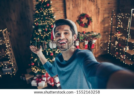 Close up photo of happy joy guy wear santa claus hat make selfie hold hand invite to his x-mas party celebration in house with christmas decoration illuminations tinsels wreath #1552163258