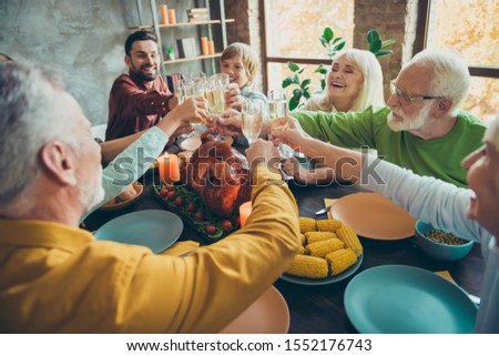 Big happy family sit table celebrate october holiday thanksgiving day hold glass of champagne clink have meal corns harvest roasted meat gathering small kids pensioners in house #1552176743