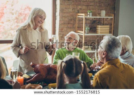 Big happy family meeting  celebrate thanksgiving day sit table enjoy meal with roasted meat poultry retired woman say toast to small little kids pensioner relatives in house #1552176815