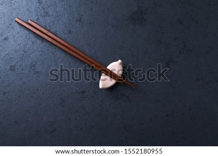 Wooden chopsticks and chopstick rest on dark stone background. Top view. Copy space.  #1552180955
