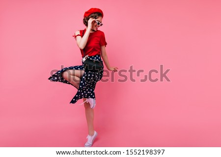 Excited brunette lady in black skirt dancing on rosy background. Appealing white girl in french beret jumping in studio. #1552198397