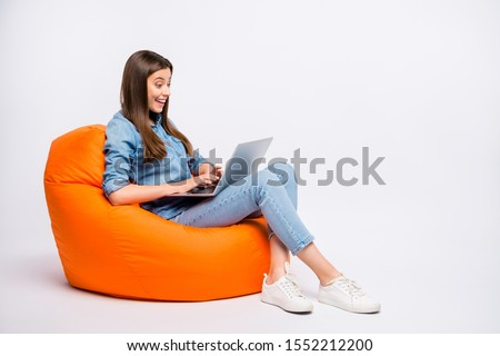 Profile side view of her she nice attractive lovely charming cheerful cheery girl sitting in bag chair using laptop isolated over light white color background #1552212200