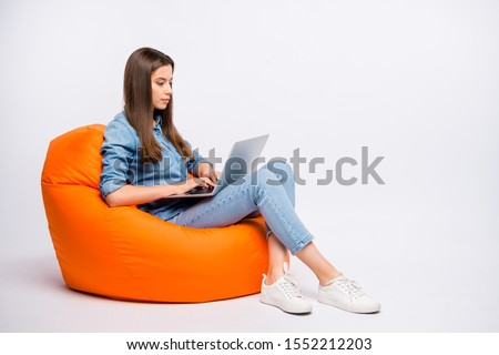 Full size profile side photo of serious concentrated girl work on her computer chat with start-up clients sit big bag lounge chair wear casual style clothing isolated over white color background