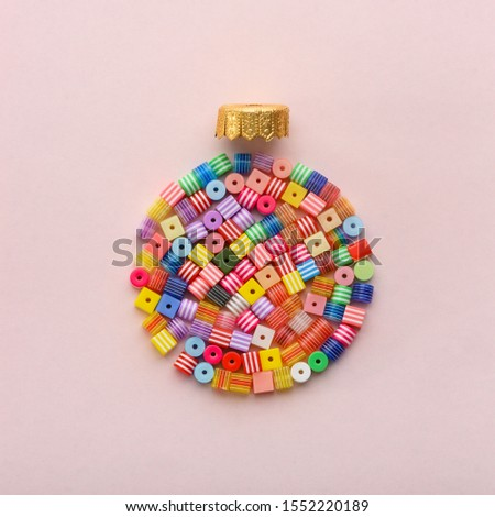 Christmas Bauble made of decoration elements on pink background. Flat lay. Contemporary design. Contemporary art. Creative conceptual and colorful collage. #1552220189