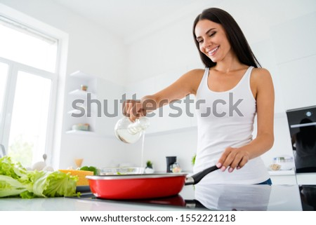 Low angle view photo of positive cheerful girl real chef want cook tasty gourmet supper pour oil on frying pan have rest relax in kitchen house indoors #1552221218