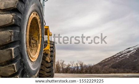 Panorama Focus on the black rubber tires of a yelow bulldozer at a construction site #1552229225