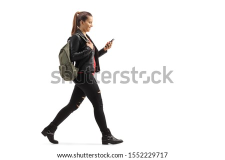 Full length profile shot of a girl with a backpack walking and looking at her mobile phone isolated on white background #1552229717