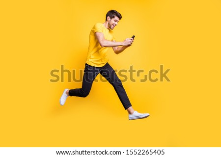 Full body photo of handsome guy jumping high holding telephone rushing romantic date typing girlfriend sms wear casual t-shirt trousers isolated yellow color background #1552265405