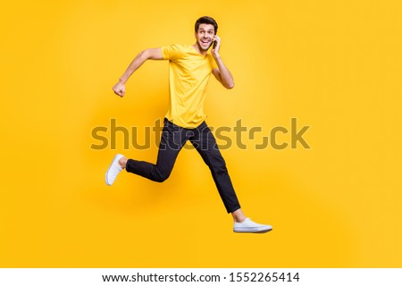 Full body photo of handsome guy jumping high talking telephone rushing romantic date see girlfriend wear casual t-shirt trousers isolated yellow color background #1552265414
