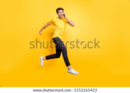 I'm on my way darling! Full body photo of handsome guy jumping high talking telephone rushing romantic date wear casual t-shirt trousers isolated yellow color background #1552265423