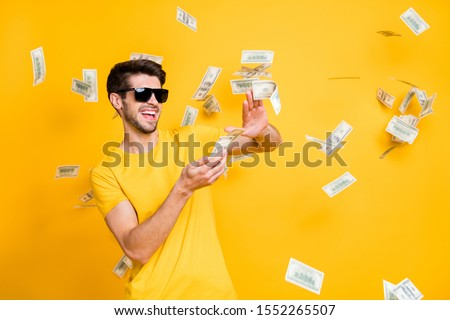 Photo of young handsome careless guy throwing usa money banknotes away wealthy person wear sun specs casual t-shirt isolated bright yellow color background #1552265507