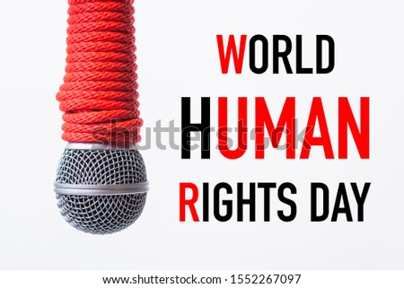 Red Rope on microphone with WORLD HUMAN RIGHTS DAY text on white background, Human rights day concept #1552267097