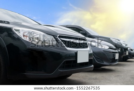 Car parked in large asphalt parking lot with cloud and blue sky background. Outdoor parking lot  travel transportation technology concept. Front view of black cars #1552267535
