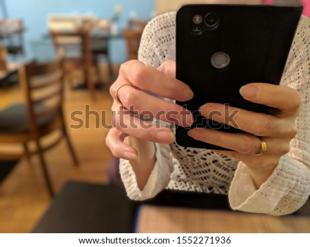 A woman sitting at a table in a restaurant using social media on her smartphone mobile app instead of talking to her companion. The background is deliberately blurred out of focus to draw attention