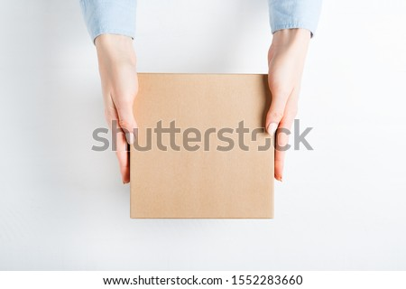 Square cardboard box in female hands. Top view, white background #1552283660