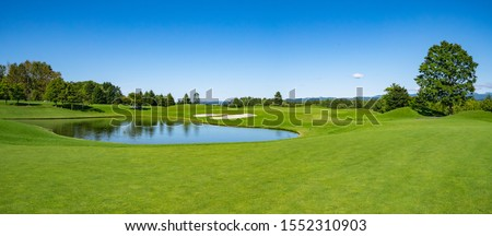 Panorama View of Golf Course with beautiful green field. Golf course with a rich green turf beautiful scenery. Royalty-Free Stock Photo #1552310903