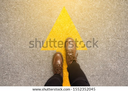 Feet and arrows on road background in starting line beginning idea. Top view. Woman in leather ankle boots on pathway with yellow direction arrow symbol. Moving forward, new start and success concept. #1552352045