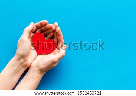Heart icon. Paper heart in hands on blue background top view space for text #1552450721