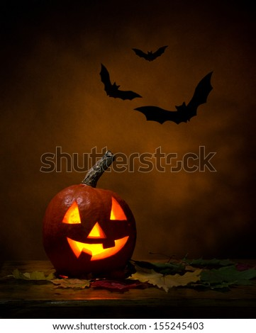 Halloween -  pumpkin and bats, maple leafs on wooden table, dark-brown background