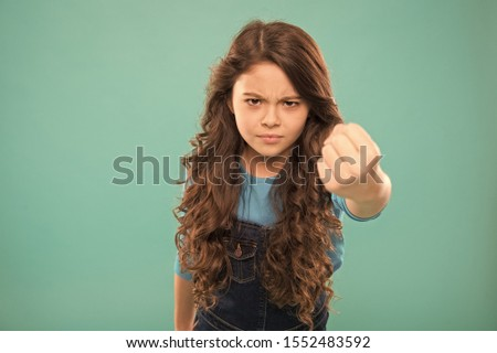 Painful punch. Serious child threatening. Punch you in face. Stop bullying movement. Girl threatening with fist. Threatening physical attack. Aggression concept. Aggressive girl threatening to beat. #1552483592
