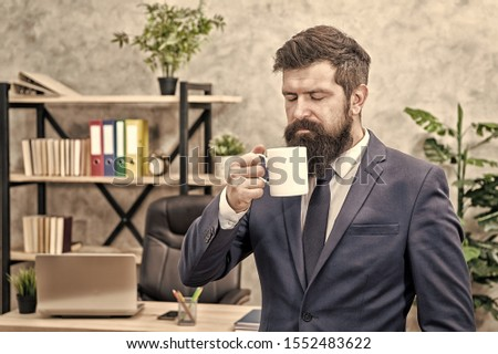 Drinking coffee relaxing break. Boss enjoying energy drink. Start day with coffee. Successful people drink coffee. Caffeine addicted. Man bearded businessman hold coffee cup stand office background. #1552483622