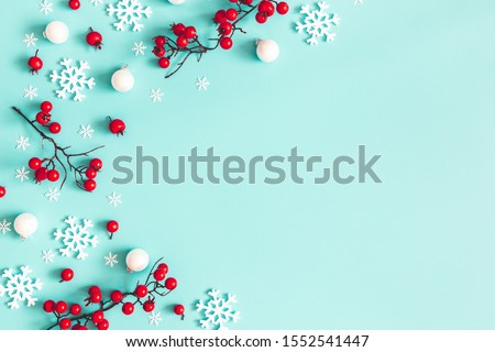 Christmas or winter composition. Snowflakes and red berries on blue background. Christmas, winter, new year concept. Flat lay, top view, copy space #1552541447
