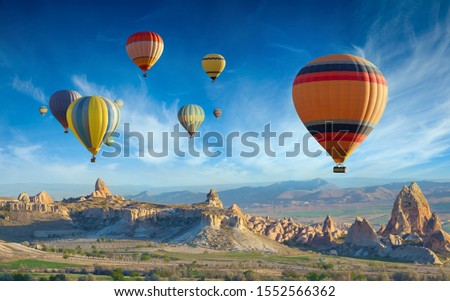 Surise view of unusual rocky landscape in Cappadocia, Turkey. Colorful hot air balloons fly in blue sky over amazing valleys with fairy chimneys in Cappadocia. #1552566362