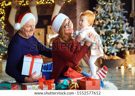 Grandmother and grandfather and girl are smiling in the house at Christmas. #1552577612